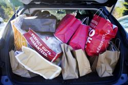 Shopping bags are stuffed into a car at Prime outlets in Lee, Mass.