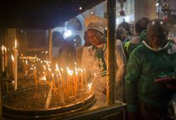 Christian worshippers light candles at the Church of the Nativity.