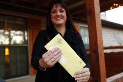Reagen Adair holds on to a RIP Medical Debt yellow envelope as she poses for a photo at her home in Murchison, Texas.