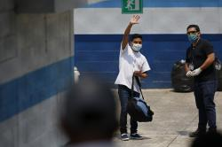 A deported man waves to his family who brought him food, at the site where Guatemalans returned from the U.S. are being held in Guatemala City, Friday, April 17, 2020.