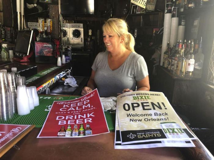 In this Friday, June 12, 2020 photo, Cherie Boos, manager of Lafitte's Blacksmith Shop Bar on Bourbon Street, stands behind the bar as workers prepare it for reopening.
