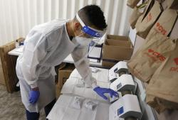 Berto Cortez, a CVS pharmacy technician, shows how COVID-19 tests are processed in a testing area set up by CVS at St. Vincent de Paul medical clinic, Monday, June 15, 2020, in Phoenix
