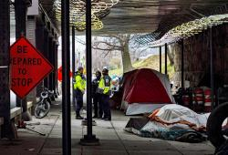 In this March 3, 2020 photo released by the University of Maryland via the Howard Center for Investigative Journalism, Washington, D.C., officials confer under a railroad overpass on L Street NE, about eight blocks from the U.S. Capitol, before garbage trucks and front loaders remove the homeless encampment there