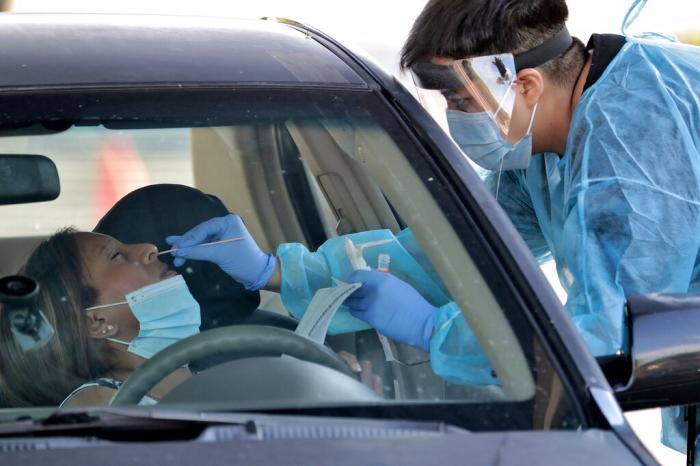 People are tested in their in vehicles in Phoenix's western neighborhood of Maryvale in Phoenix for free COVID-19 tests organized by Equality Health Foundation.