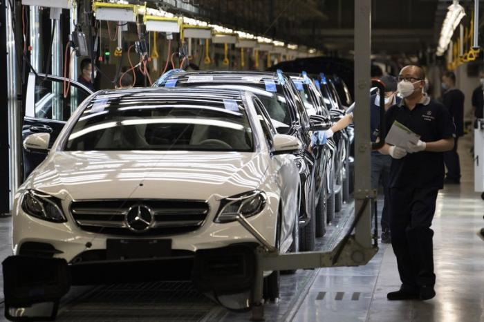 Workers inspect newly assembled cars at a Beijing Benz Automotive Co. Ltd factory, a German joint venture company for Mercedes-Benz, in Beijing on Wednesday, May 13, 2020