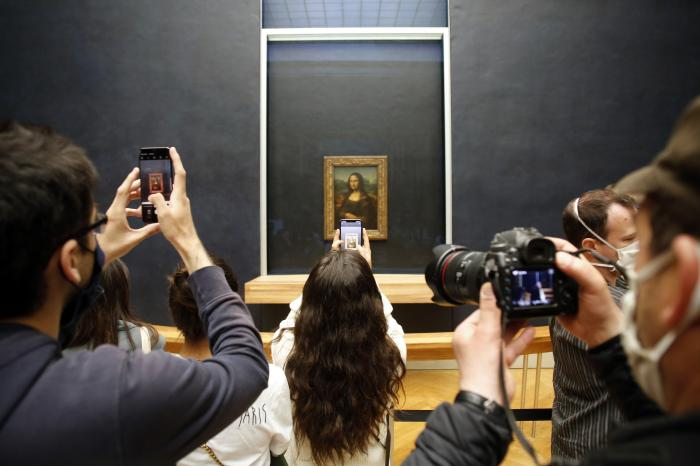 Visitors take photos of the Leonardo da Vinci's painting Mona Lisa, in Paris.