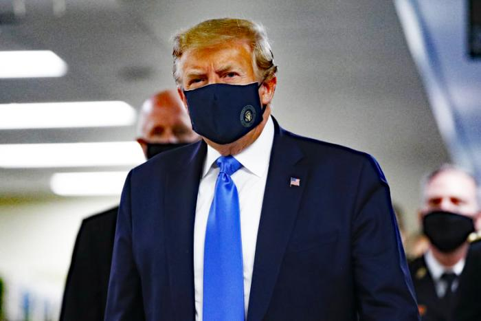 President Donald Trump wears a mask as he walks down the hallway during his visit to Walter Reed National Military Medical Center in Bethesda, Md., Saturday, July 11, 2020