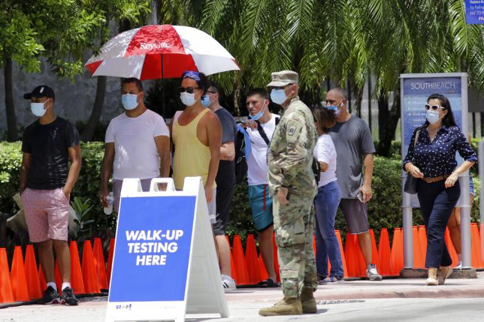 People wait in line at a walk-up testing site for COVID-19 during the new coronavirus pandemic, in Miami Beach, Fla.