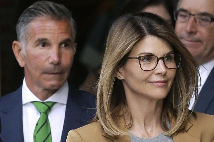 Actress Lori Loughlin, front, and husband, clothing designer Mossimo Giannulli, left, depart federal court in Boston
