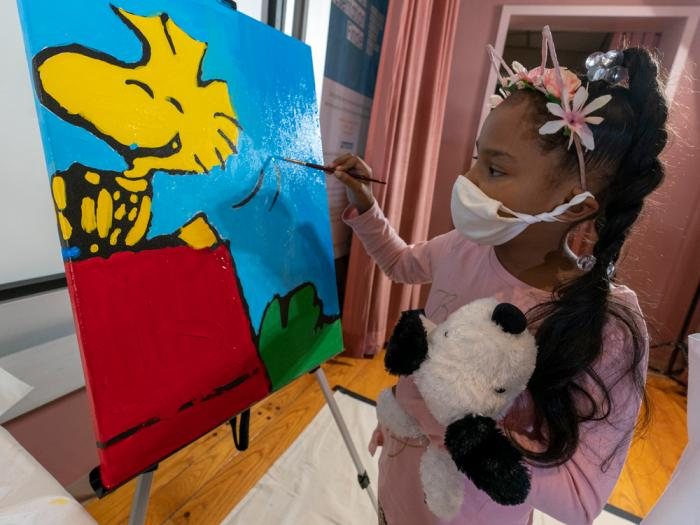 """Kaley Williams, 8, paints a panel of a """"Peanuts"""" mural that will be placed in the outpatient pediatric floor of One Brooklyn Health at Brookdale Hospital, Thursday, Oct. 1, 2020, in the Brooklyn borough of New York"""