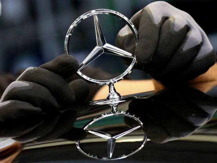 In this Thursday, April 30, 2020 file photo, an employee attaches a Mercedes emblem as he works on a Mercedes-Benz S-class car at the Mercedes plant in Sindelfingen, Germany