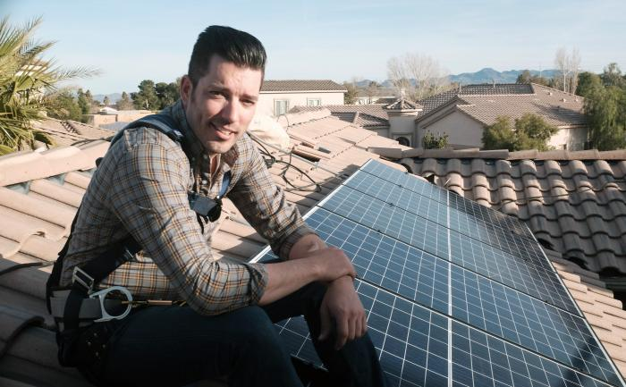 """This image released by Independent Lens shows Jonathan Scott from """"Property Brothers"""" installing solar panels on a rooftop in his new documentary """"Jonathan Scott's Power Trip."""""""