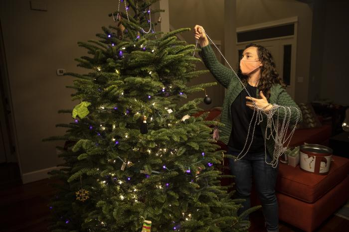 Ani Sirois puts lights and decorations on the family's Christmas tree at her home on Tuesday, Nov. 24, 2020 in Portland, Ore.