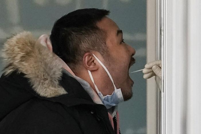 A man gets a swab for the coronavirus test at a hospital in Beijing.