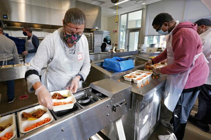 Volunteers Sheeran Howard, left, and Ibrahim Bahrr, right, package meals at Community Servings, which prepares and delivers scratch-made, medically tailored meals to individuals & families living with critical & chronic illnesses.