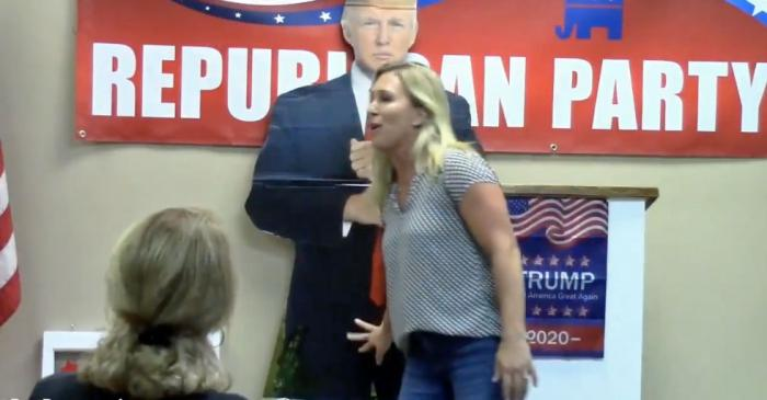 Marjorie Taylor Greene gropes a life-size Trump cut-out.