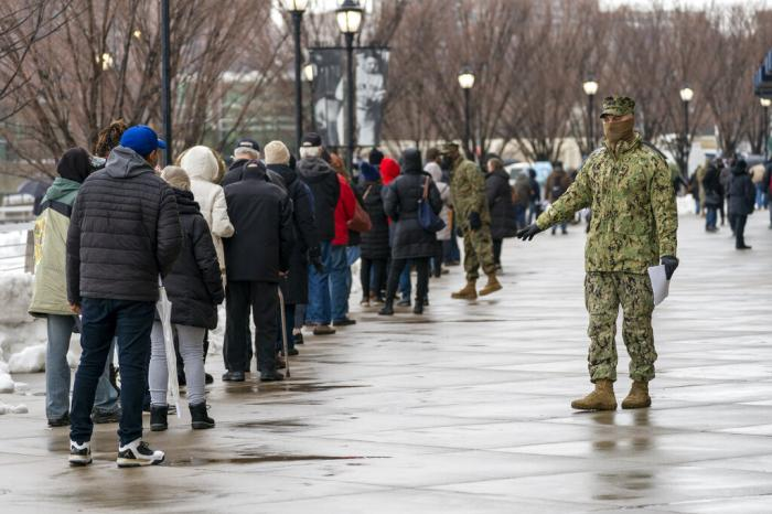A member of the National Guard gives people direction standing in line at a COVID-19 vaccination site at Yankee Stadium.