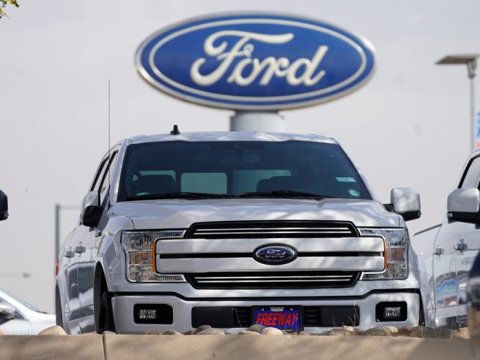 In this Sunday, Oct. 11, 2020, file photo, a row of 2020 sports-utility vehicles pickup trucks sits at a Ford dealership, in Denver