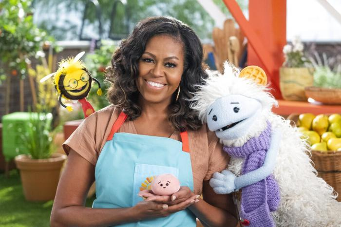 Former first lady Michelle Obama with Busy, a bee puppet, left, Mochi, a pink round puppet, and Waffles, a furry puppet with waffle ears.