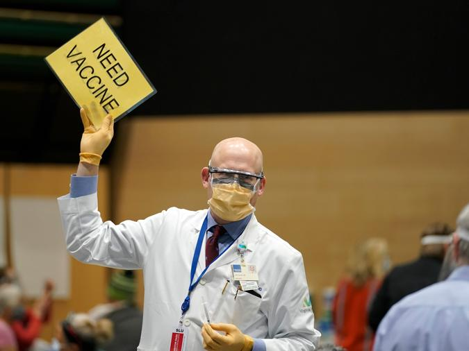"""In this Jan. 24, 2021, file photo, Dr. John Corman, the chief clinical officer for Virginia Mason Franciscan Health, holds a sign that reads """"Need Vaccine"""" to signal workers to bring him more doses of the Pfizer vaccine for COVID-19 in Seattle"""