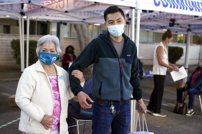 Hoa Pham, left, walks with her grandson Daniel Tran after receiving her second dose of Pfizer's COVID-19 vaccine at Families Together of Orange County Community Health Center.