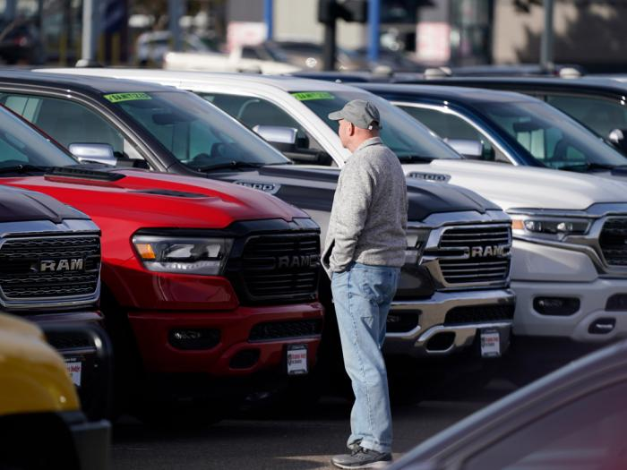 A prospective buyer surveys a long row of unsold 2020 pickup trucks at a Ram dealership, Sunday, Dec. 27, 2020, in Littleton, Colo.