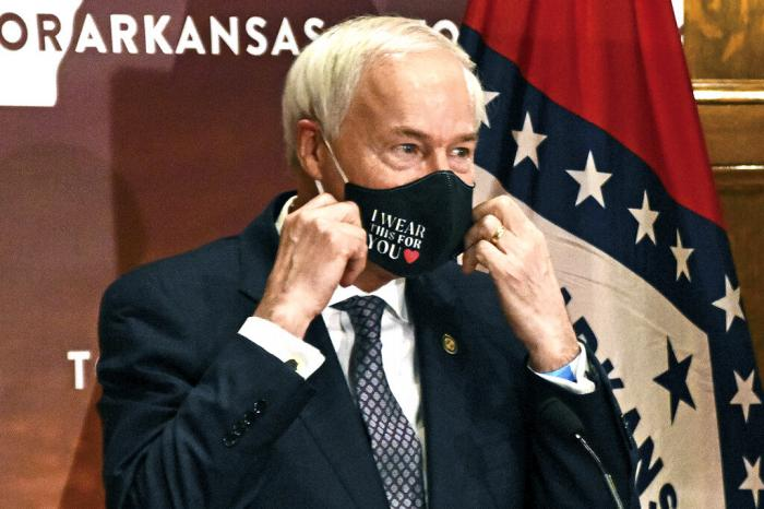 Arkansas Gov. Asa Hutchinson removes his mask before a briefing at the state capitol in Little Rock.