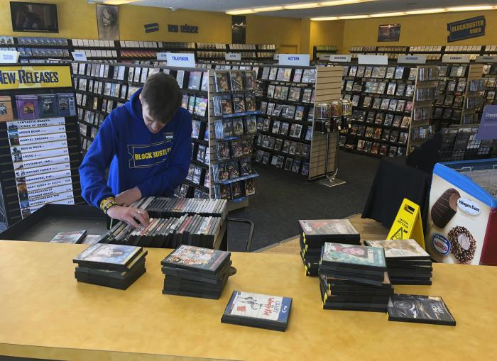 Employee Ryan Larrew alphabetizes returned movies before re-shelving them at the last Blockbuster store on the planet in Bend, Ore.