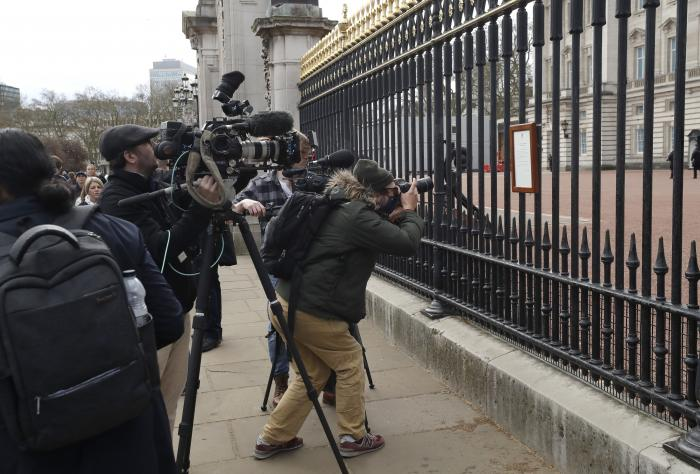 In this Friday, April 9, 2021 file photo, members of the media take images of an announcement, regarding the death of Britain's Prince Philip, displayed on the fence of Buckingham Palace in London.