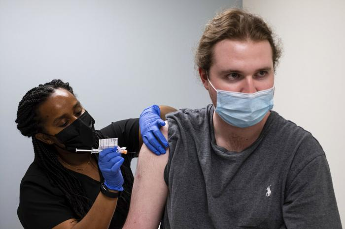 Cole Smith receives a Moderna variant vaccine shot from clinical research nurse Tigisty Girmay at Emory University's Hope Cliniic.