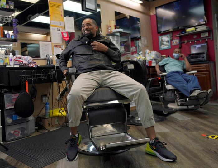 Mike Brown, a barber and health advocate, reacts while talking with colleagues and customers, Friday, April 9, 2021, in Hyattsville, Md.