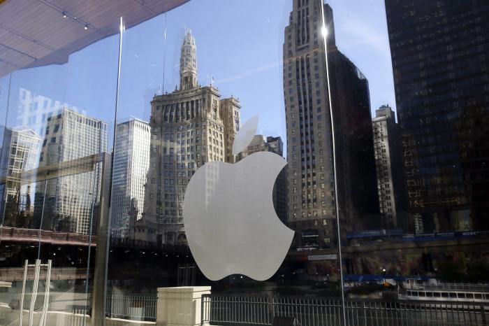 Buildings are reflected behind the logo at an Apple Store in downtown Chicago.