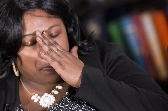 In this Dec, 15, 2014 file photo, Samaria Rice, of Cleveland, Ohio, mother of Tamir Rice, touches her hand to her face during an interview at The Associated Press, in New York