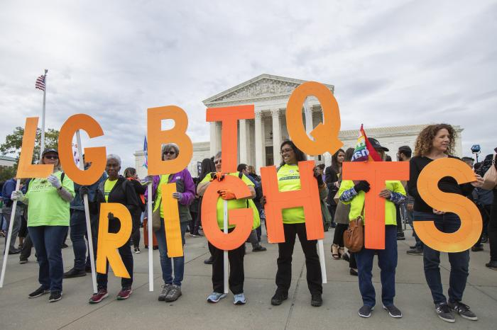 Supporters of LGBTQ rights hold placards in front of the U.S. Supreme Court, on Capitol Hill in Washington.
