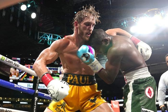 Logan Paul, left and Floyd Mayweather fight during an exhibition boxing match at Hard Rock Stadium.