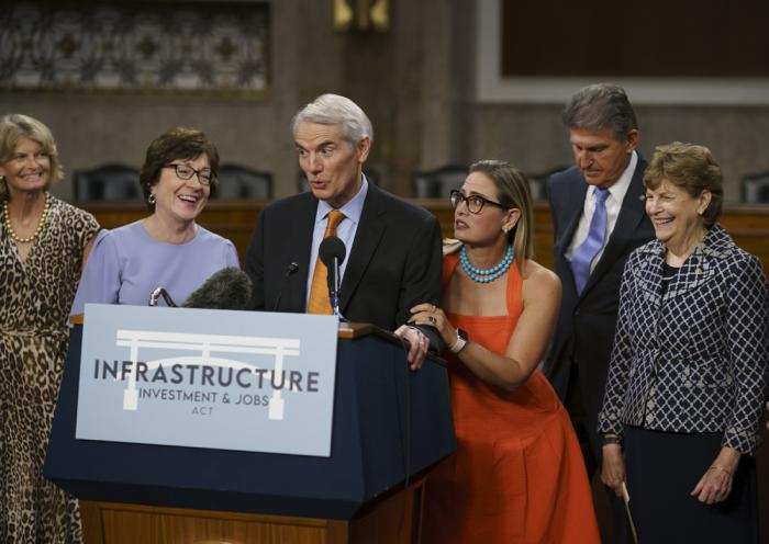The bipartisan group of Senate negotiators speak to reporters just after a vote to start work on a nearly $1 trillion bipartisan infrastructure package, at the Capitol in Washington, Wednesday, July 28, 2021