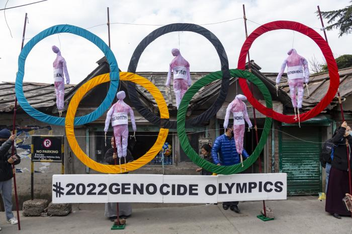 In this Feb. 3, 2021, file photo, exile Tibetans use the Olympic rings as a prop as they hold a protest against the holding of the 2022 Beijing Winter Olympics, in Dharmsala, India