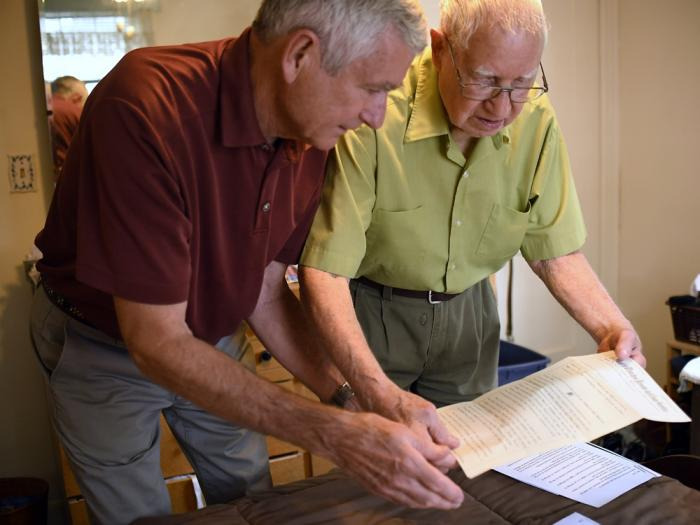 In this Saturday, July 17, 2021, photo, Dave Ware, left, and his father, Fred Ware, look over a deed and copy of a covenant for their home in Manchester, Conn.