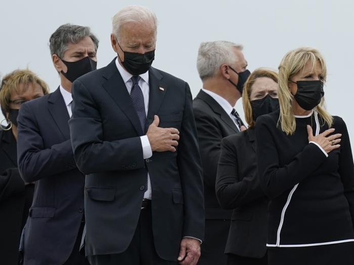 President Joe Biden and first lady Jill Biden watch as a carry team moves the transfer case containing the remains of Navy Corpsman Maxton W. Soviak, 22, of Berlin Heights, Ohio, during a casualty return Sunday, Aug. 29, 2021, at Dover Air Force Base, Del.